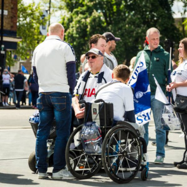 London, UK - 12 May, 2019: color image depicting disabled football supporters in wheelchairs outside the brand new modern architecture of the Tottenham Hotspur stadium in north London, UK. It is the day of an English Premier League match (Tottenham v Everton) and the fans are eager to explore the surroundings of the new stadium. Room for copy space.