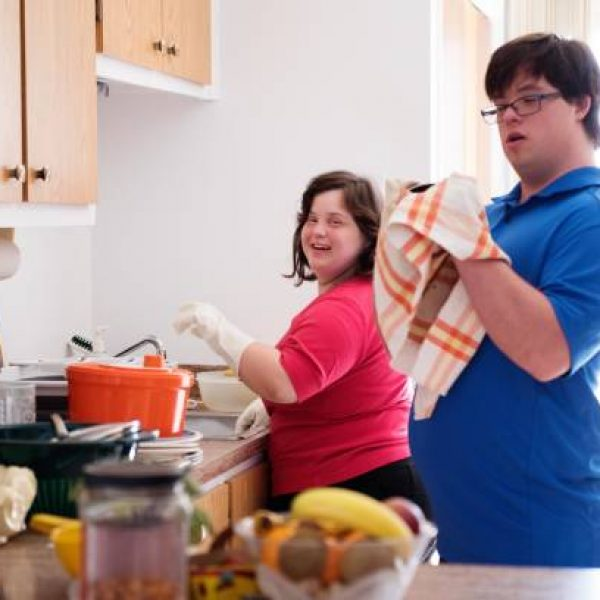 Couple in love of 26 years old Down Syndrome at her apartment in Montreal. They are learning to live in an apartment independently. They are washing the dishes together. Color and horizontal photo was taken in Quebec Canada.
