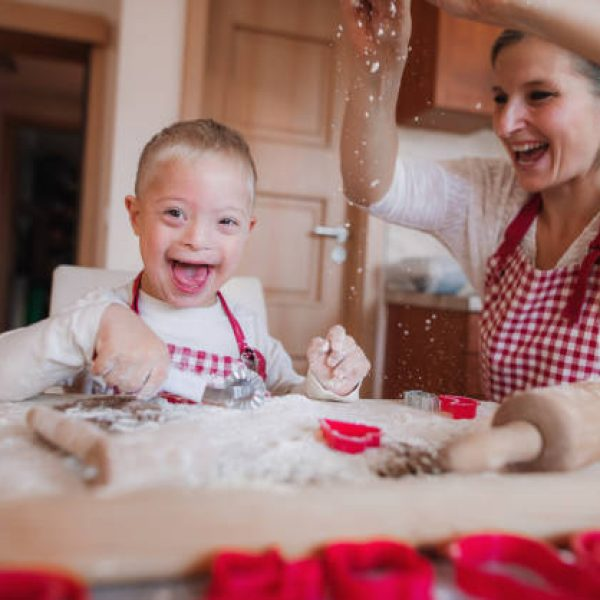 A laughing handicapped down syndrome child and his mother with checked aprons indoors baking in a kitchen, having fun.