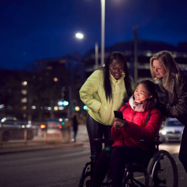 Woman In Wheelchair Having Night Out With Friends In City Ordering Taxi Using Mobile Phone App