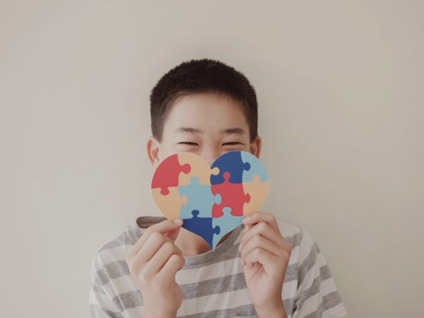 Preteen boy holding puzzle jigsaw,  child mental health concept, world autism awareness day, teen autism spectrum disorder awareness concept